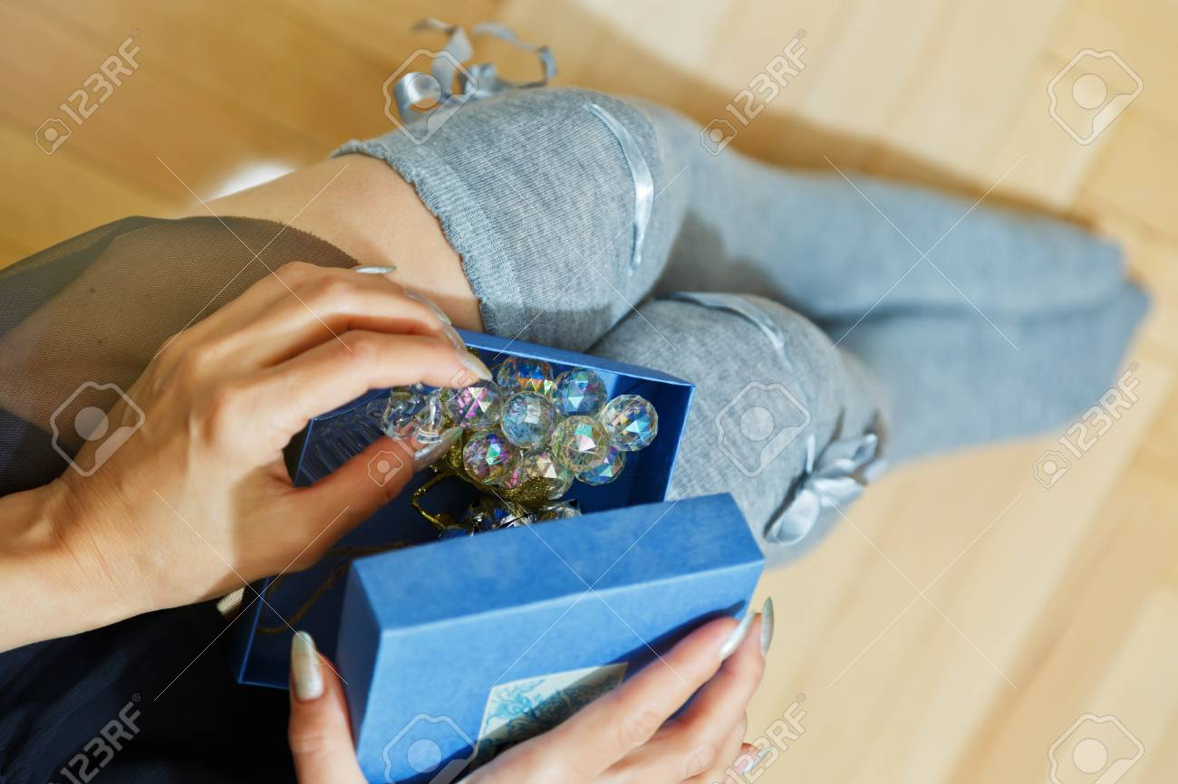 Young Adult Woman In Knee Heights Socks Opening A Box With Gift Holding It On Her Knees Holiday Present Concept Suitable For Saint Valentine Day Or