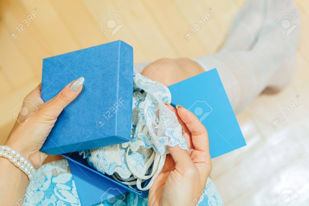5622da12a White young adult woman opening a present box on her knees with lacy sexy  lingerie item. Romantic private gift from boyfriend or husband concept for  ...