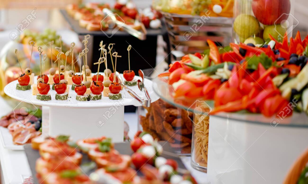 Catering. The table is richly richly filled with various snacks and vegetables. Focus on tomato and cheese snacks. High quality photo - 151178185
