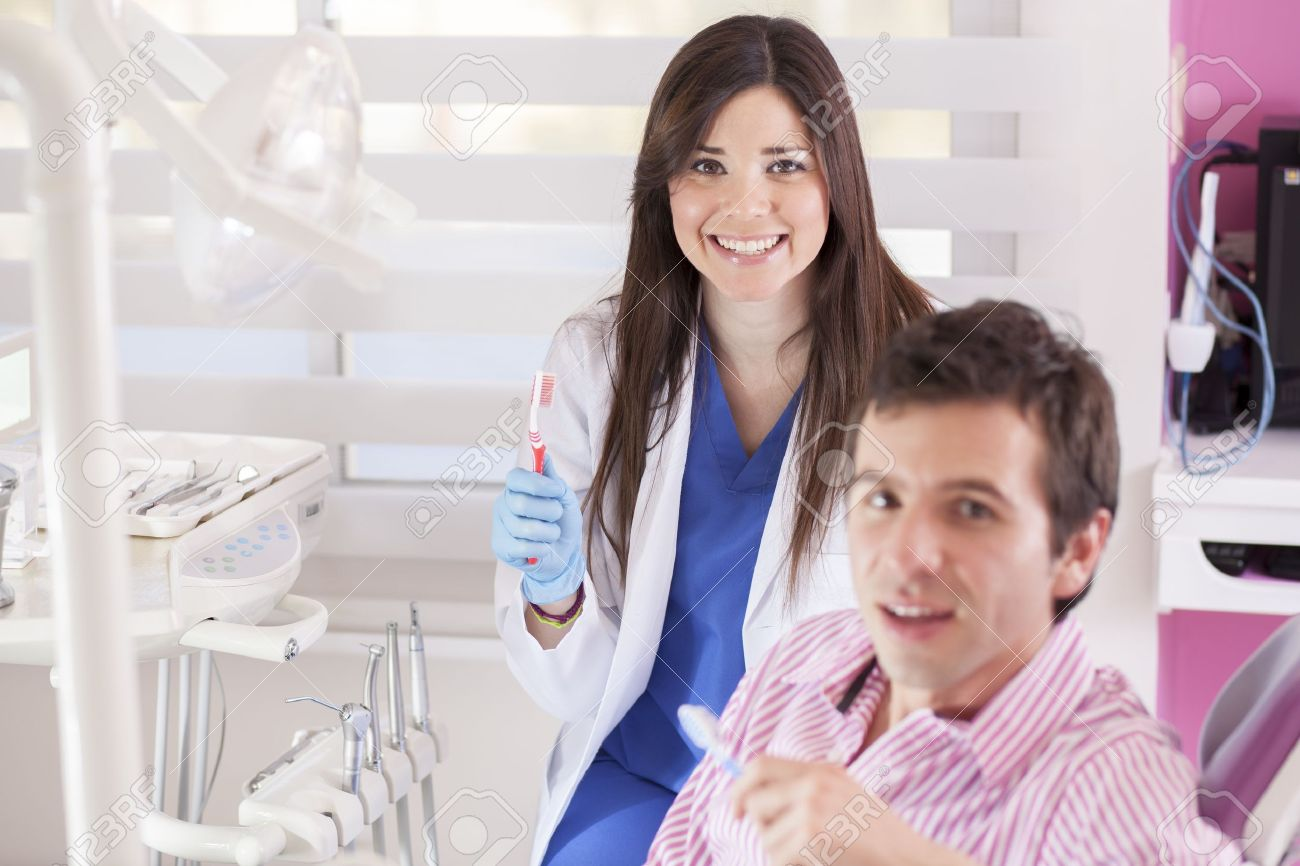 Cute female dentist and patient holding a toothbrush and smiling Stock Photo - 18253331