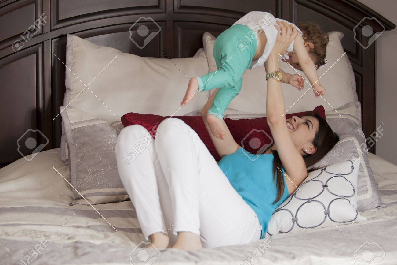 Young mother and her baby girl having fun in the bedroom Stock Photo - 18639626