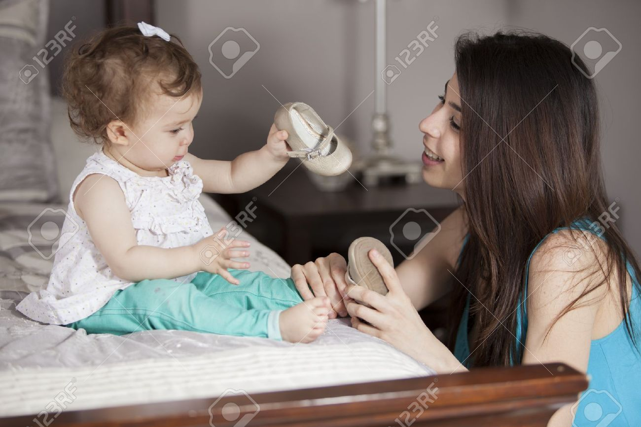 Young mom getting her baby girl dressed Stock Photo - 18639845