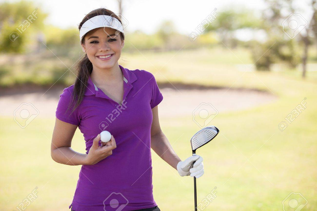 Beautiful young woman holding a golf ball and a club and smiling Stock Photo - 19382950