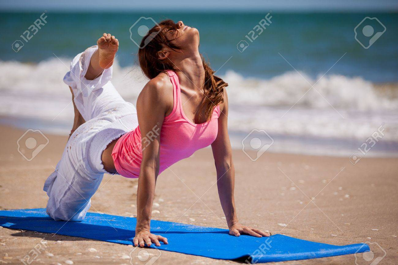 Gorgeous Hispanic woman trying a new yoga pose in the beach Stock Photo - 19912980