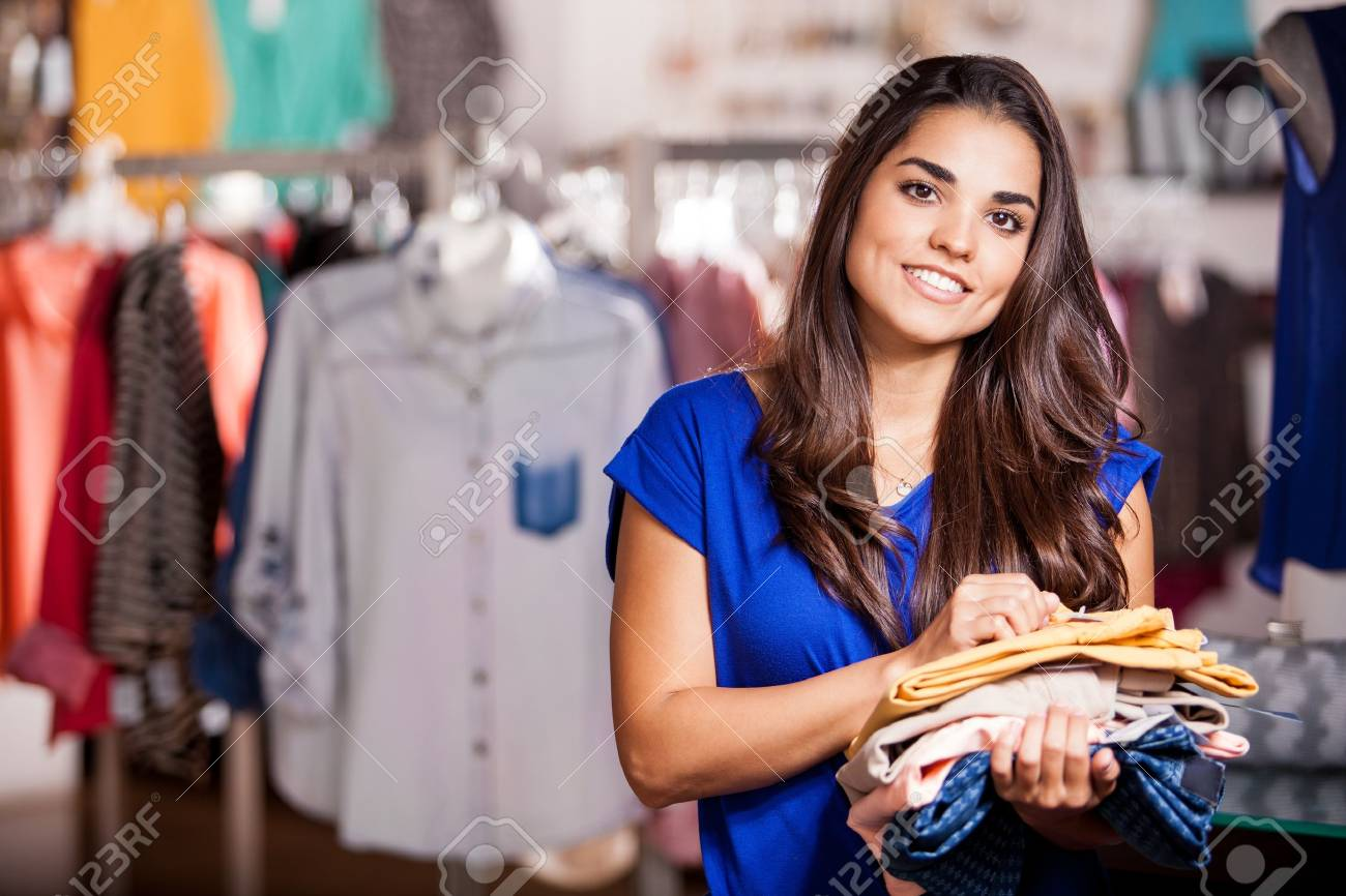 48783f563d7 Stock Photo - Wider shot of a beautiful young woman shopping some clothes  in a clothing store and smiling