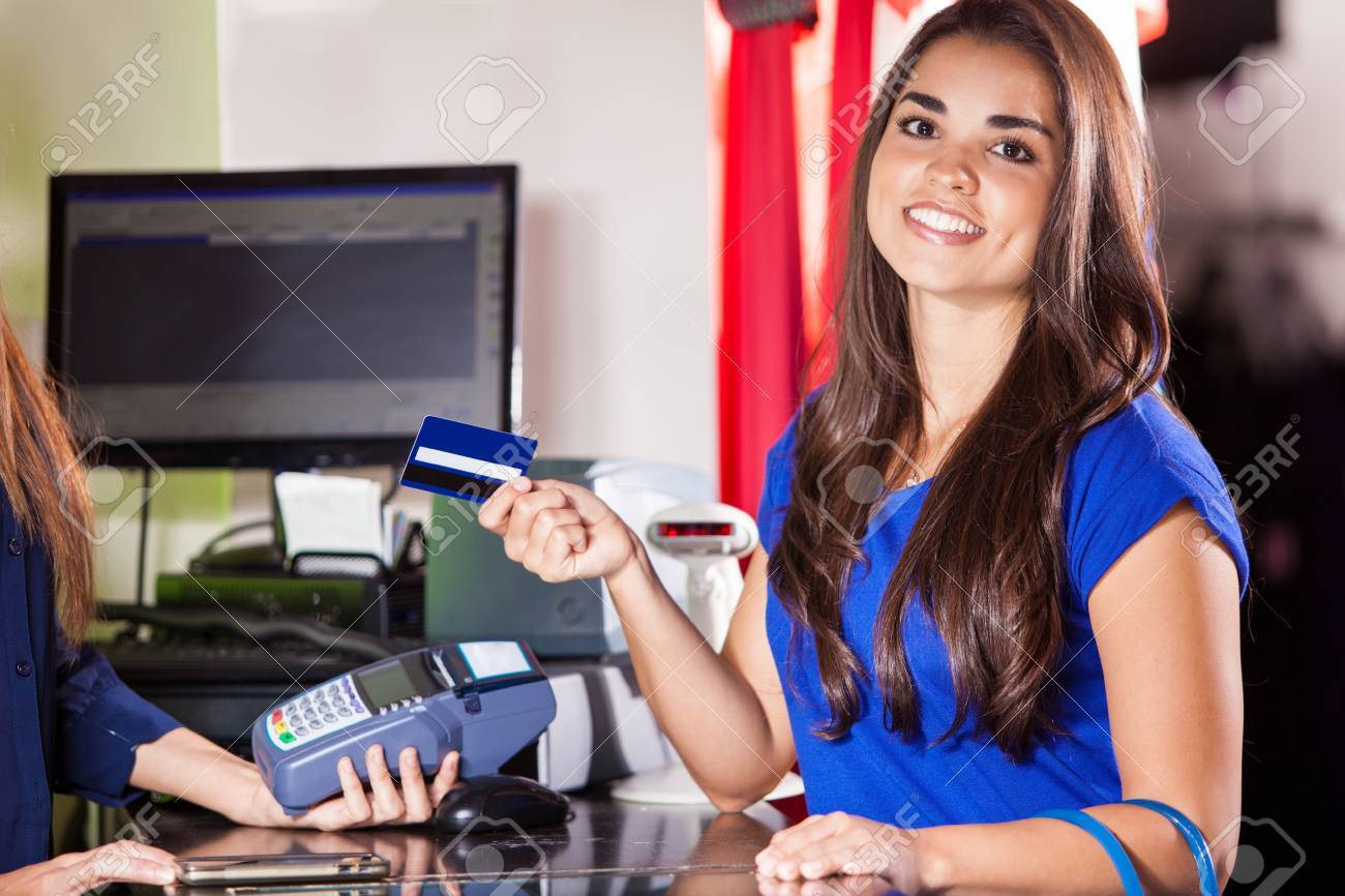 Beautiful Hispanic Woman Paying With A Credit Card At A Clothing