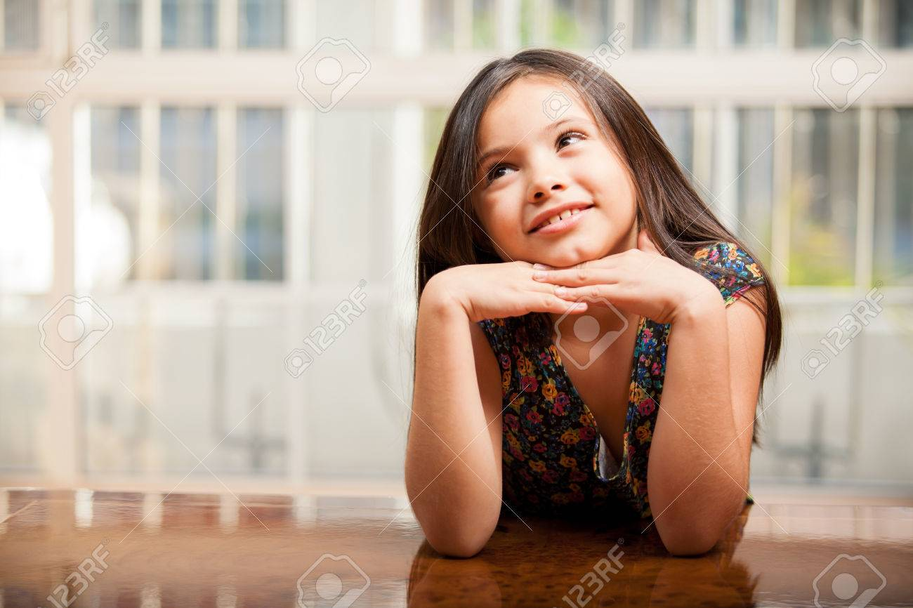 Happy little brunette daydreaming and looking towards copy space Stock Photo - 22568629
