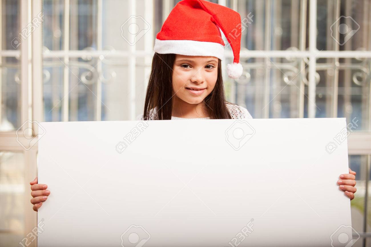 Happy little girl wearing Santa s hat and holding a big sign at home Stock Photo - 22568639