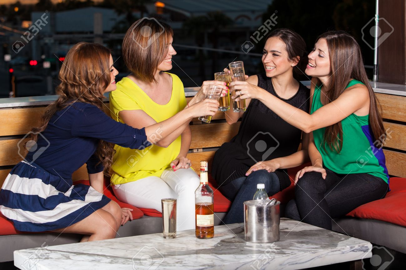 Cute female friends having fun and drinks at a restaurant at night Stock Photo - 23562638