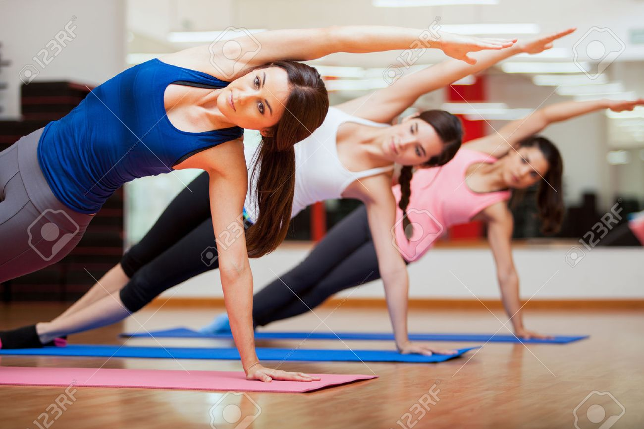 Beautiful Group Of Women Practicing The Side Plank Yoga Pose During A Class In Gym