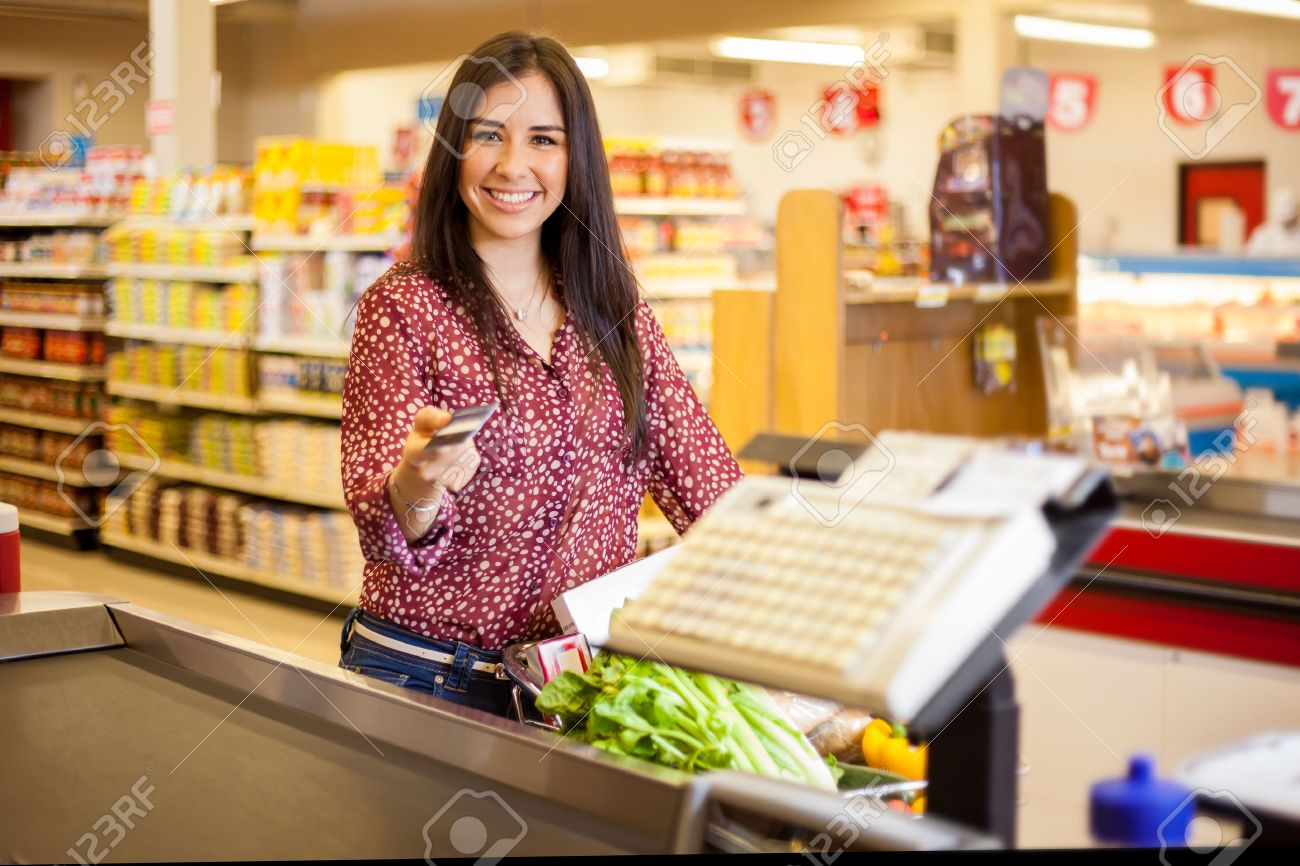 Beautiful young woman at the cash register of a supermarket paying with a credit card and smiling Stock Photo - 26683514