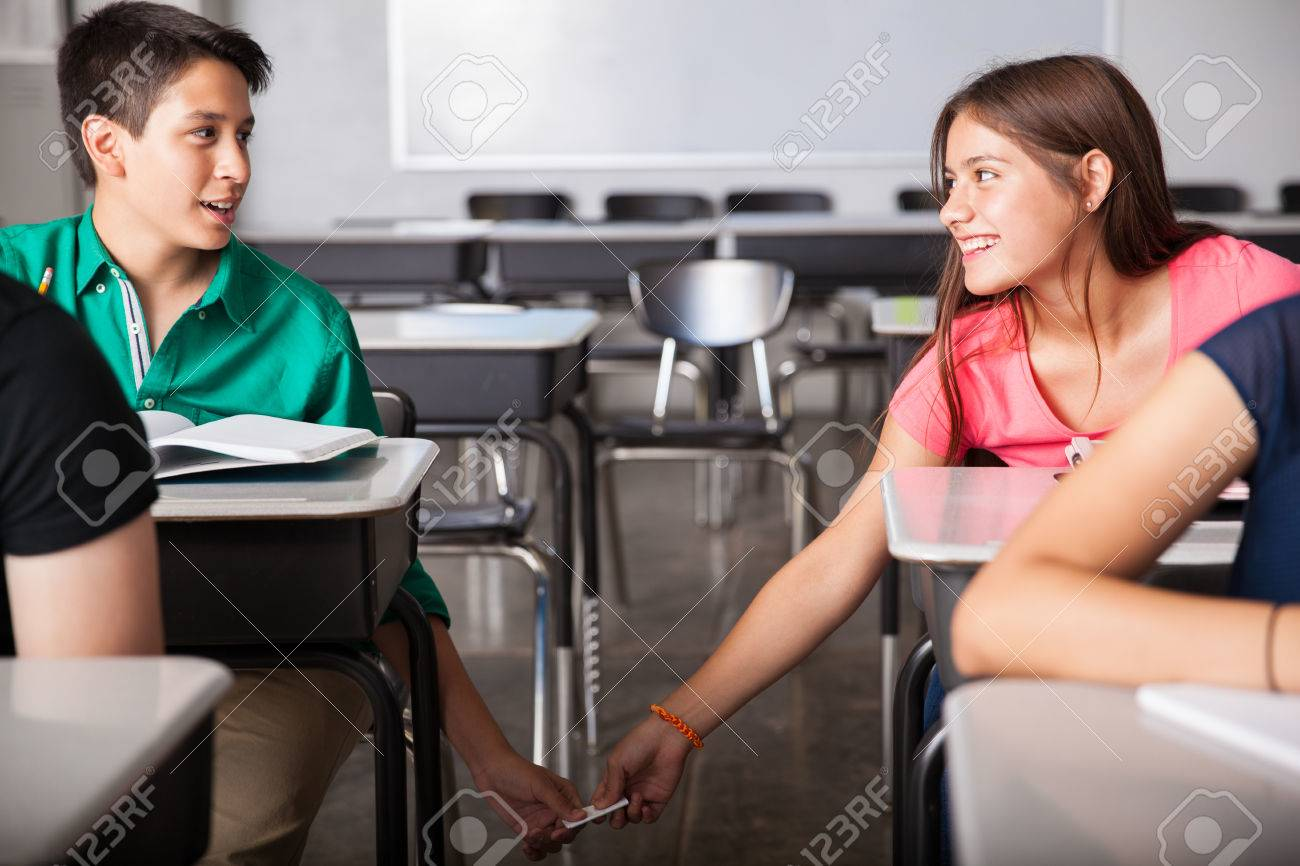 Cute couple of teens exchanging love notes and flirting in a classroom  Stock Photo - 29346744