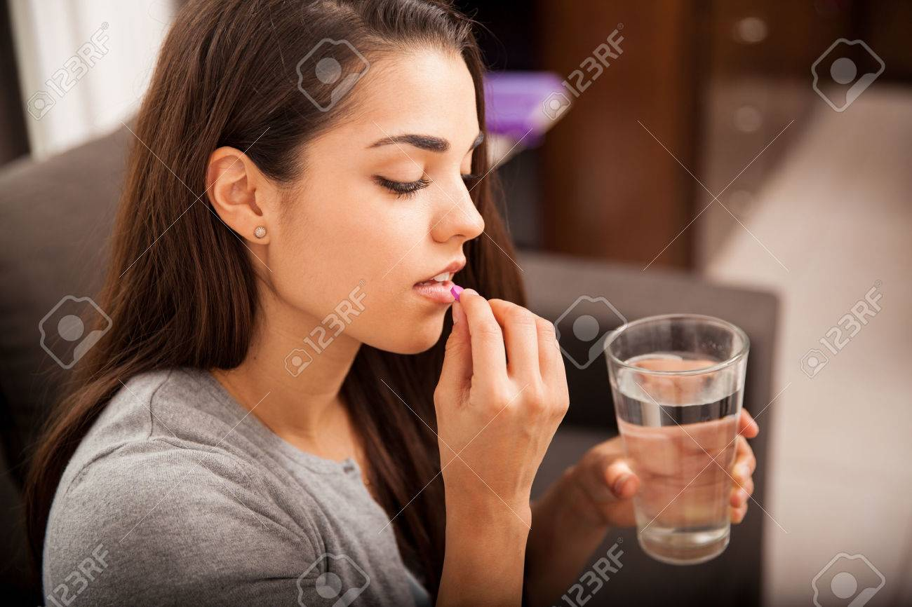 Cute young brunette taking a pill with a glass of water at home - 33909710