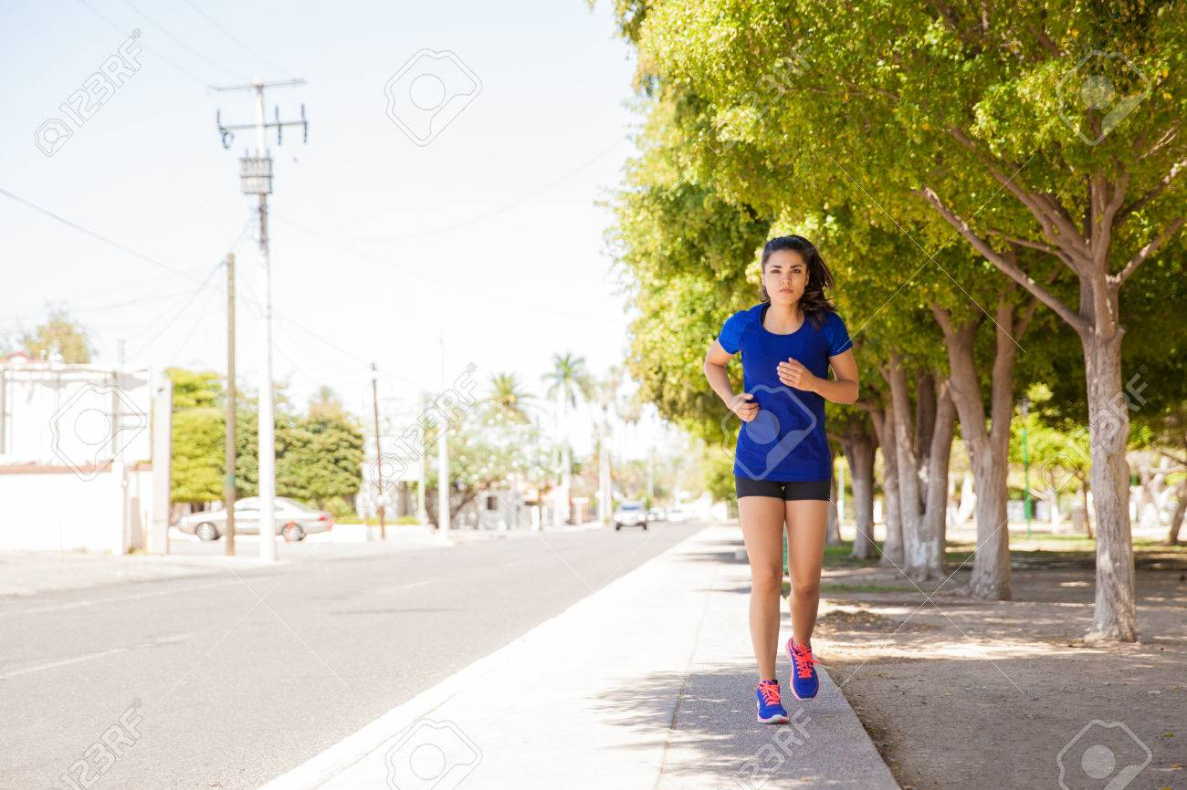 Full length portrait of a woman jogging outdoors on a park on a bright and sunny day. Lots of copy space - 40390704