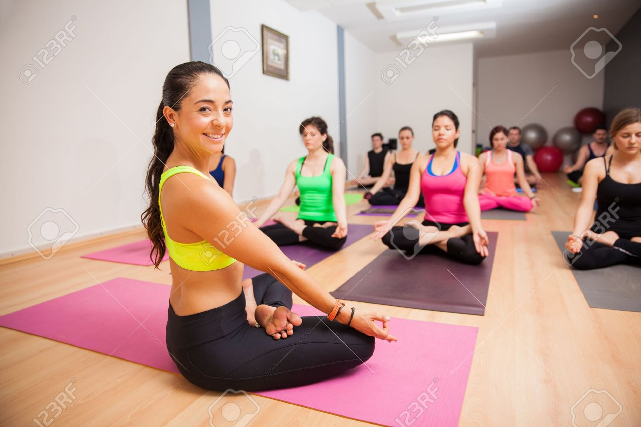 Portrait Of A Beautiful Young Yoga Instructor Smiling During One Her Classes Stock Photo
