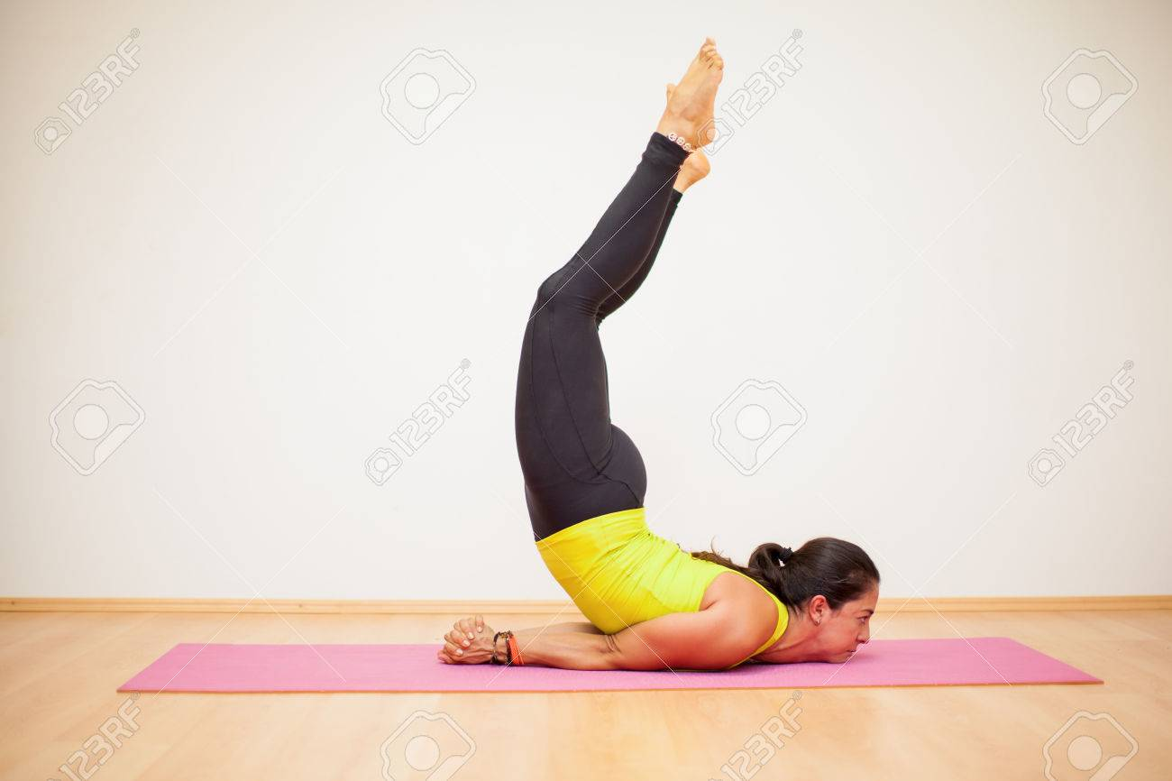 30a1201bfaa0e Stock Photo - Strong and flexible woman doing a scorpion pose with no hands  in a yoga studio