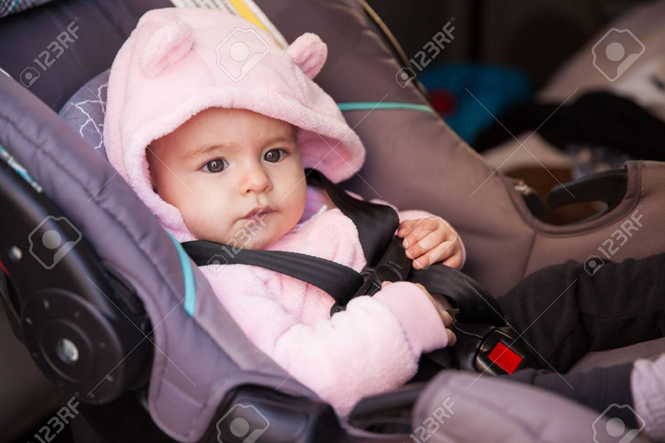 pretty baby girl with a hat sitting on a child seat in a car.. stock