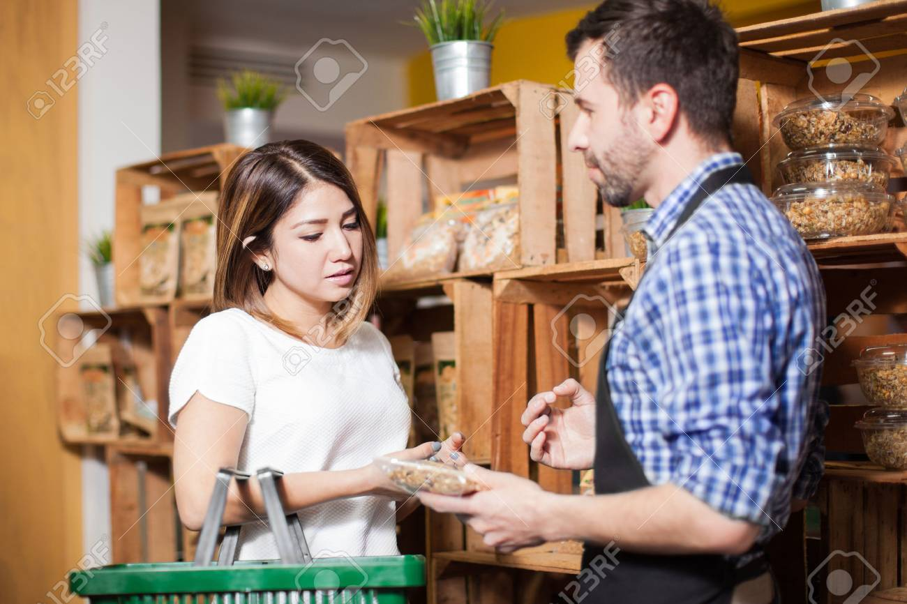 Cute brunette getting some assistance from a store clerk at a local grocery store - 52087134