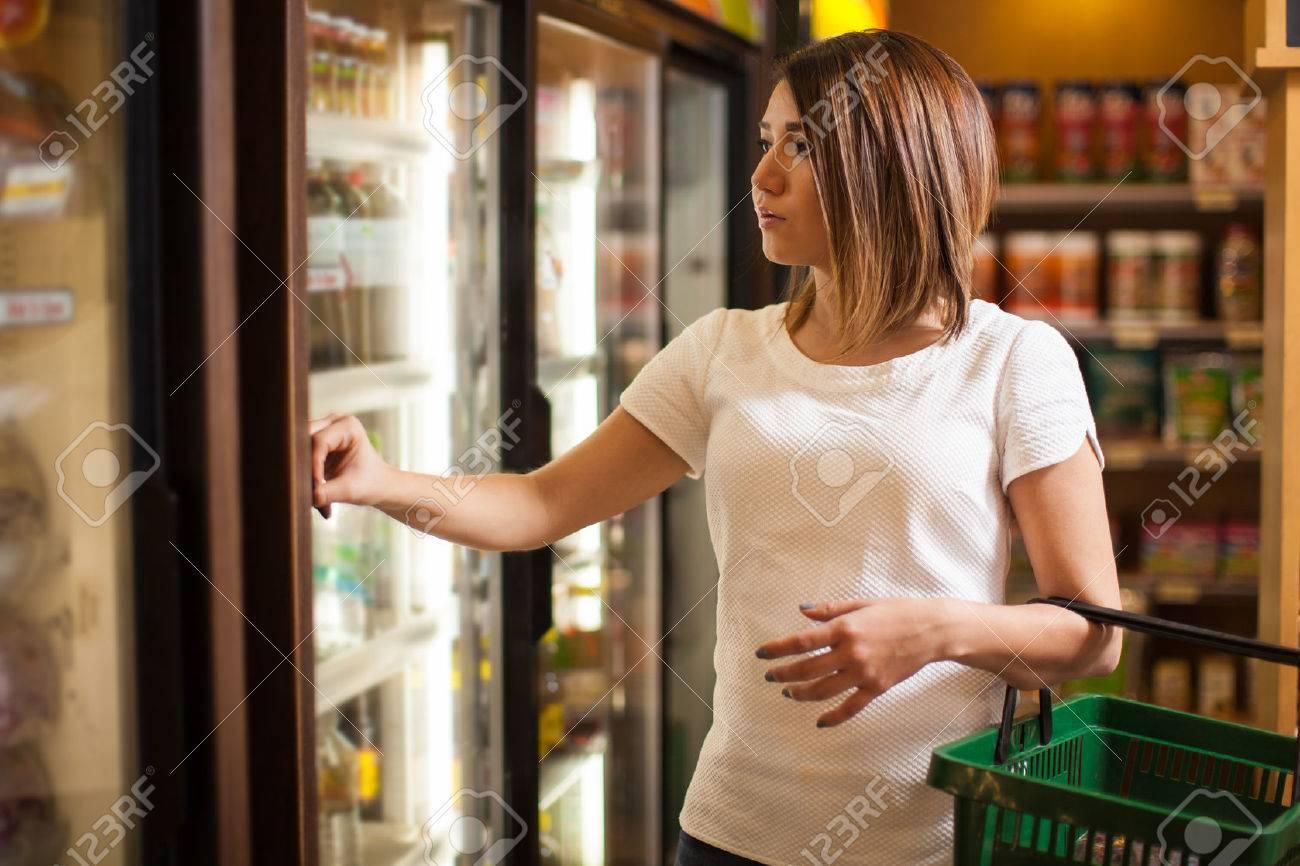 Kühlschrank Korb : Hübsche junge frau mit einem korb und einen blick auf einige