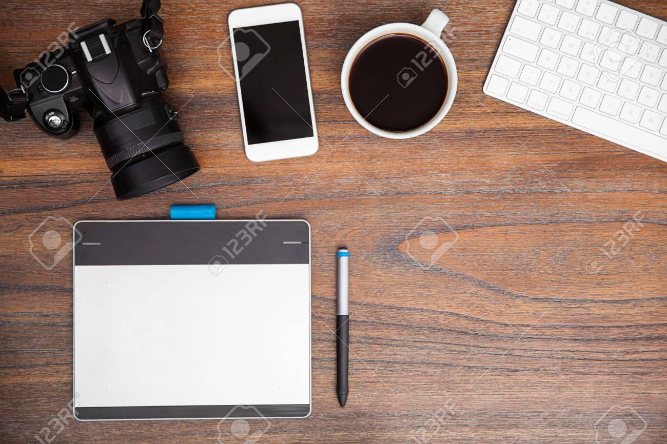 Bureau en bois avec une tablette à stylet un dslr et un
