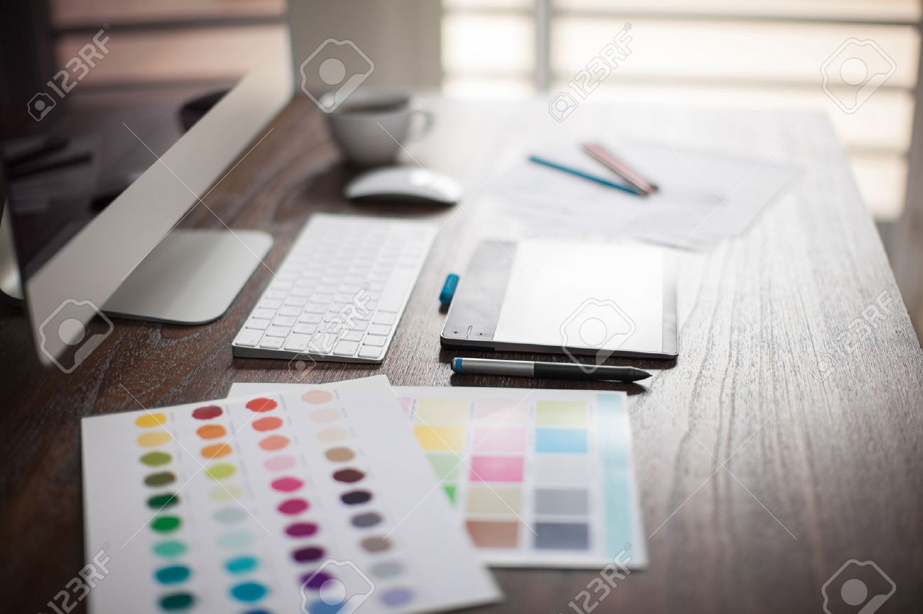 Computer, pen tablet, color swatches and sketches on a designer's workspace with a very shallow depth of field - 52580876