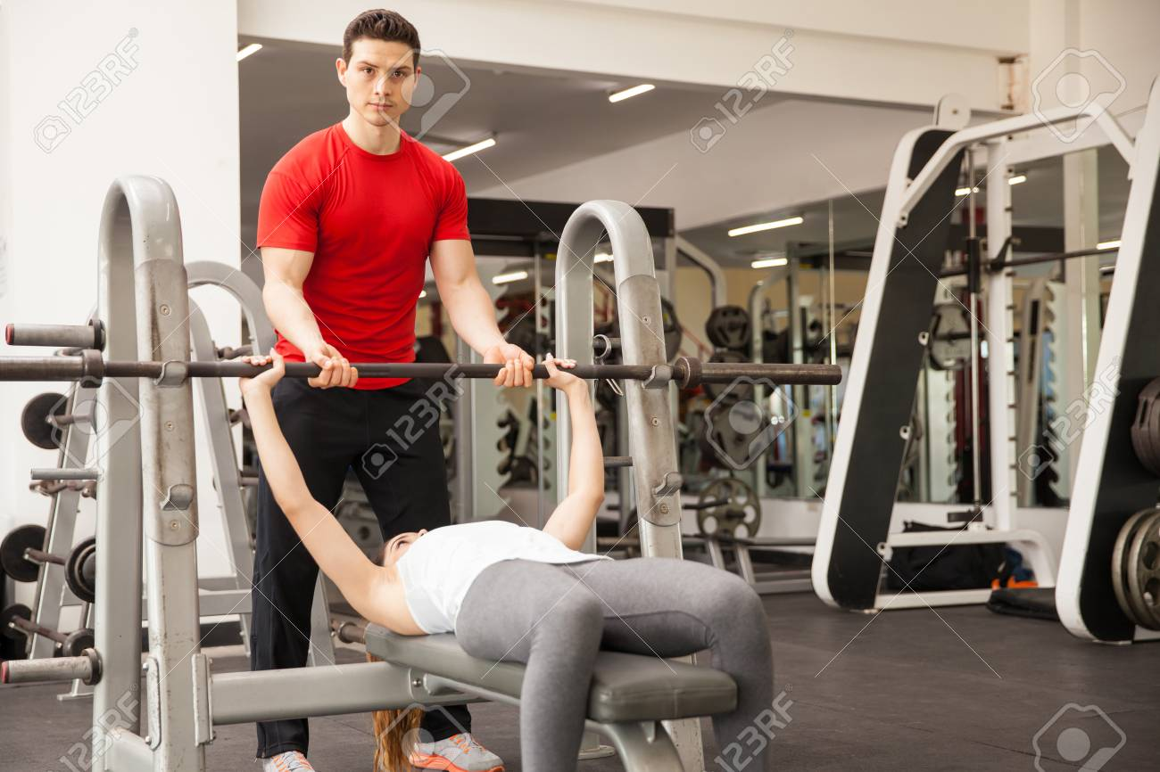 Portrait Of A Handsome Personal Trainer Spotting A Woman While She Lifts A  Barbell In The
