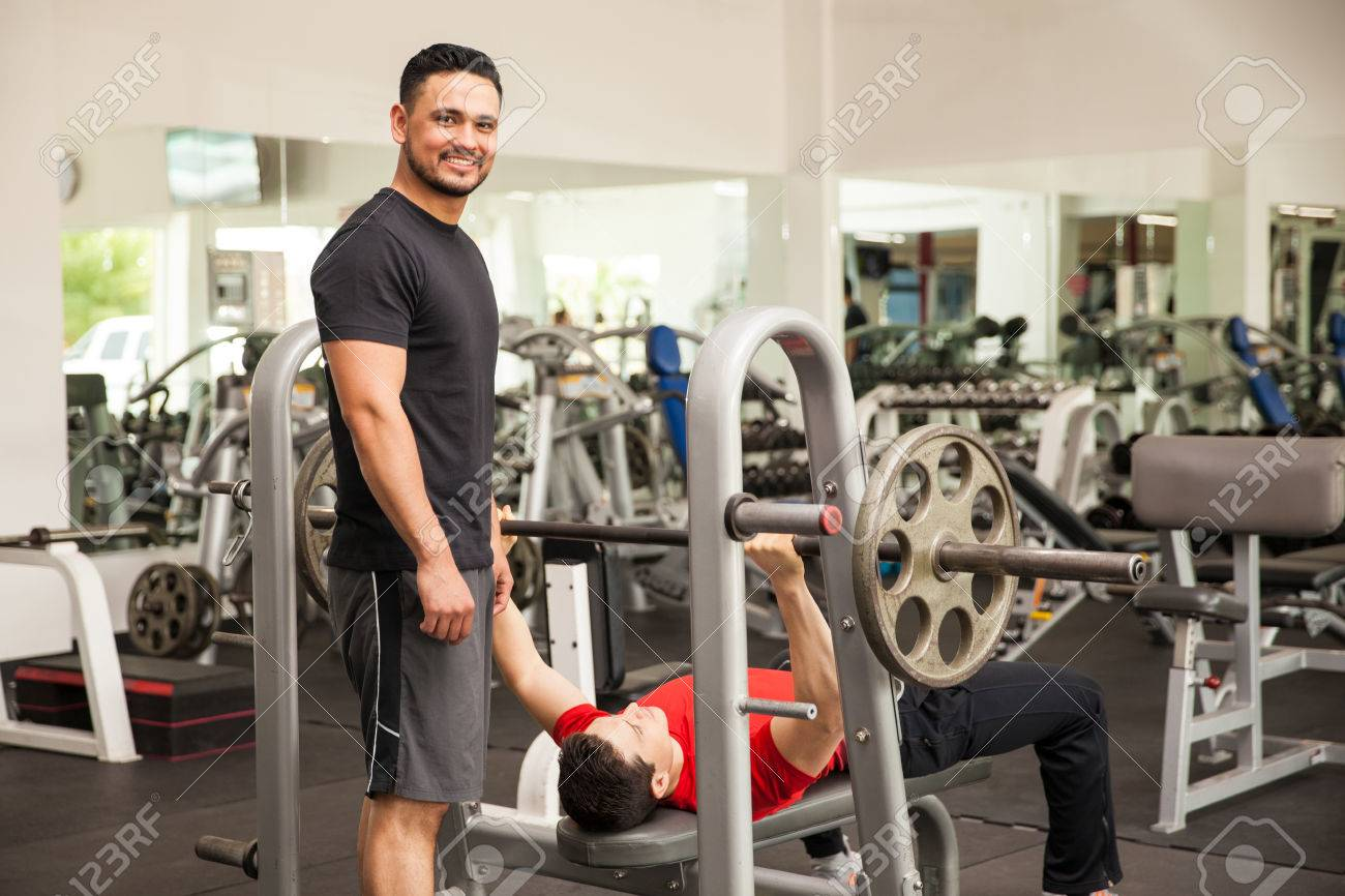 Portrait Of A Handsome Young Hispanic Man Spotting His Friend On The Bench  Press While Working