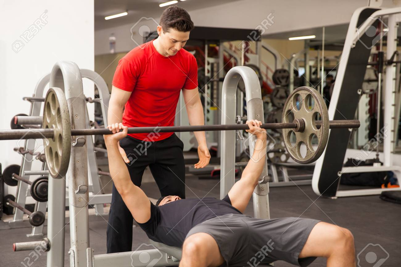Athletic Young Man Spotting A Friend While He Lifts Some Weights On A Bench  Press At