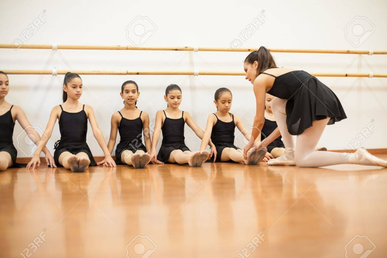 f0e90640dd0 Stock Photo - Young female dance teacher helping their students during  class at a dance academy