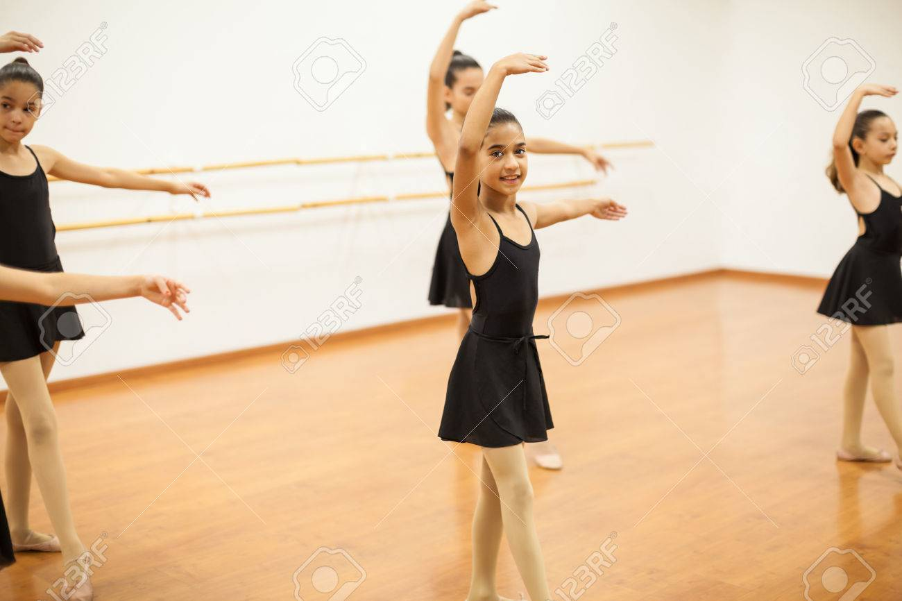 f81ef8bf352d84 Portrait of a cute girl in leotard and skirt participating in a dance class  and smiling