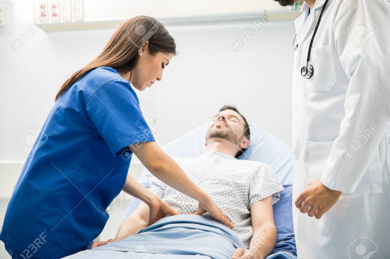 Pretty female doctor in scrubs touching the abdomen of an unconscious