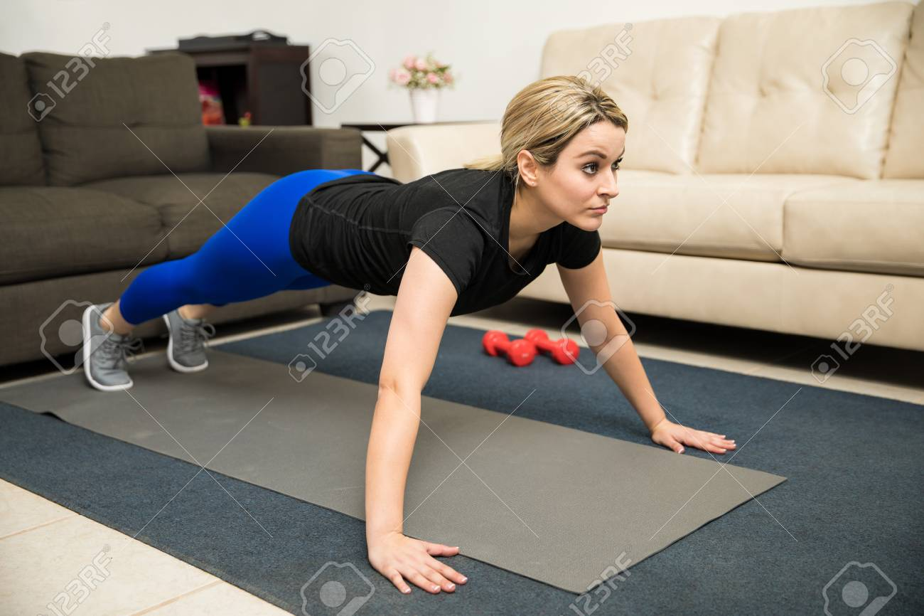 Good looking young Latin woman doing push ups at home on an exercise