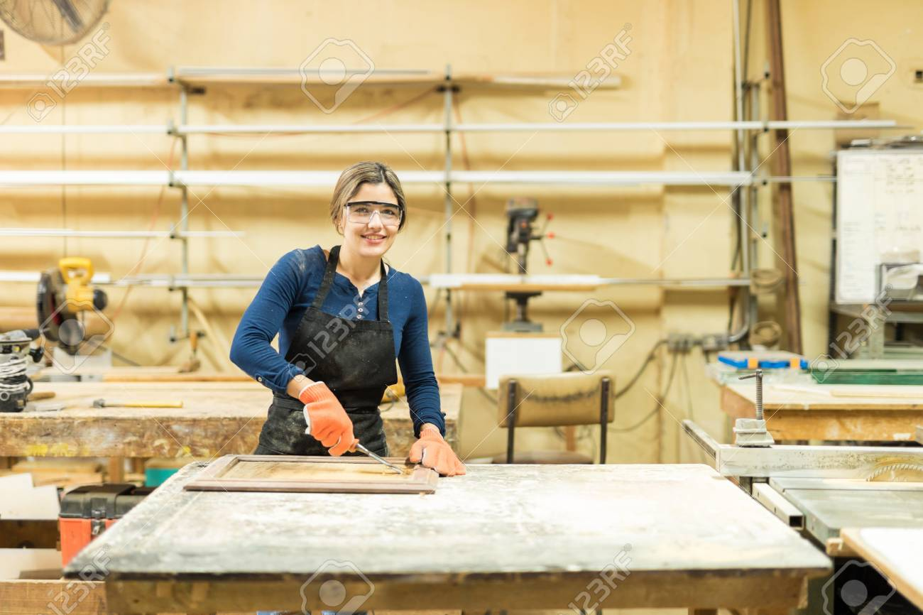 Bon Portrait Of A Cute Hispanic Female Carpenter Working On A Cabinet Door,  Using A Wood