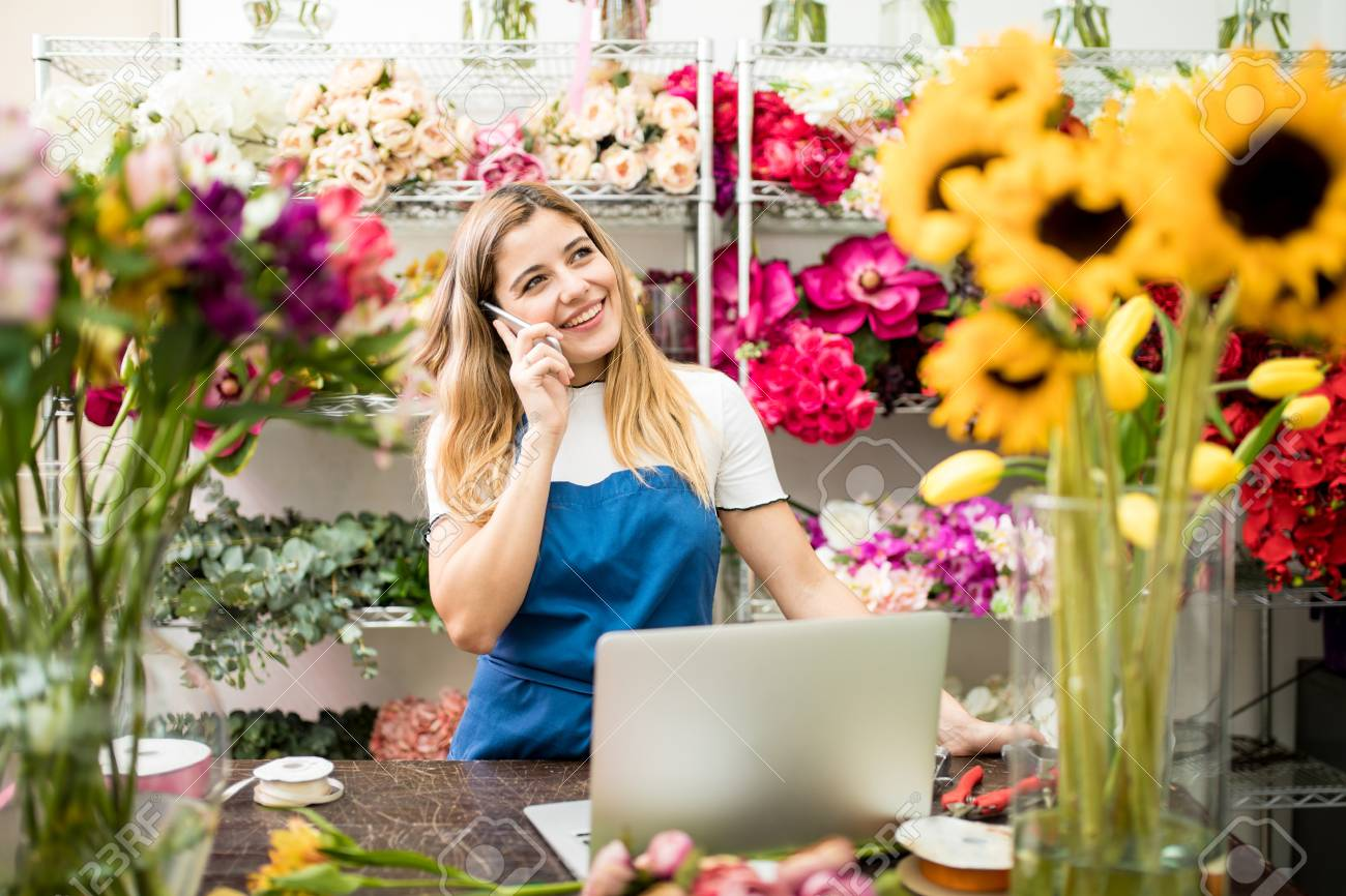 Happy Hispanic flower shop owner taking a costumer order on the phone while working on her  sc 1 st  123RF.com & Happy Hispanic Flower Shop Owner Taking A Costumer Order On The ...