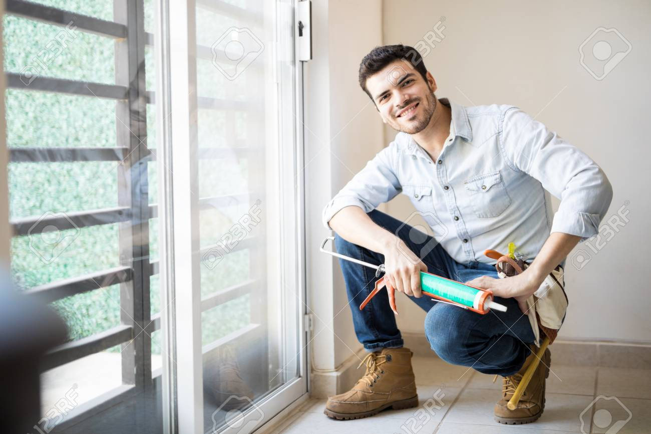 Good looking young handyman just finished sealing a door frame and looking satisfied with his work  sc 1 st  123RF.com & Good Looking Young Handyman Just Finished Sealing A Door Frame ...