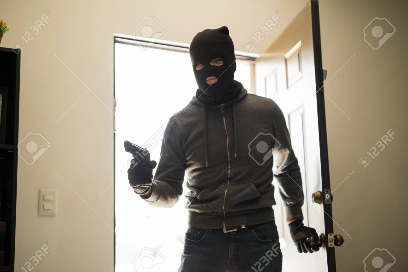 Burglar with a gun and a ski mask on the front door of a house before & Burglar With A Gun And A Ski Mask On The Front Door Of A House ...