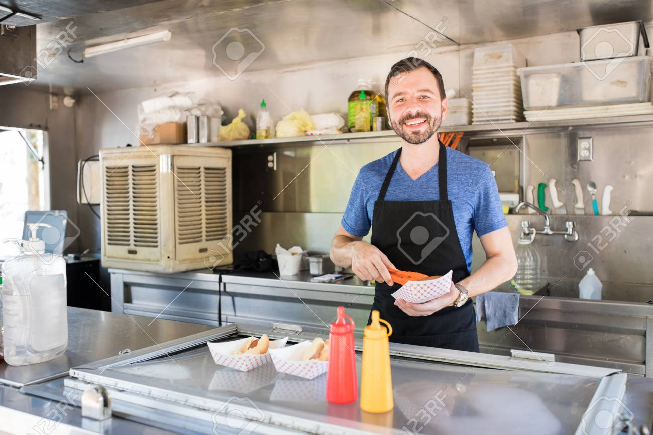 Portrait of a good looking Hispanic man preparing some hot dogs in a food stand and smiling - 89713831