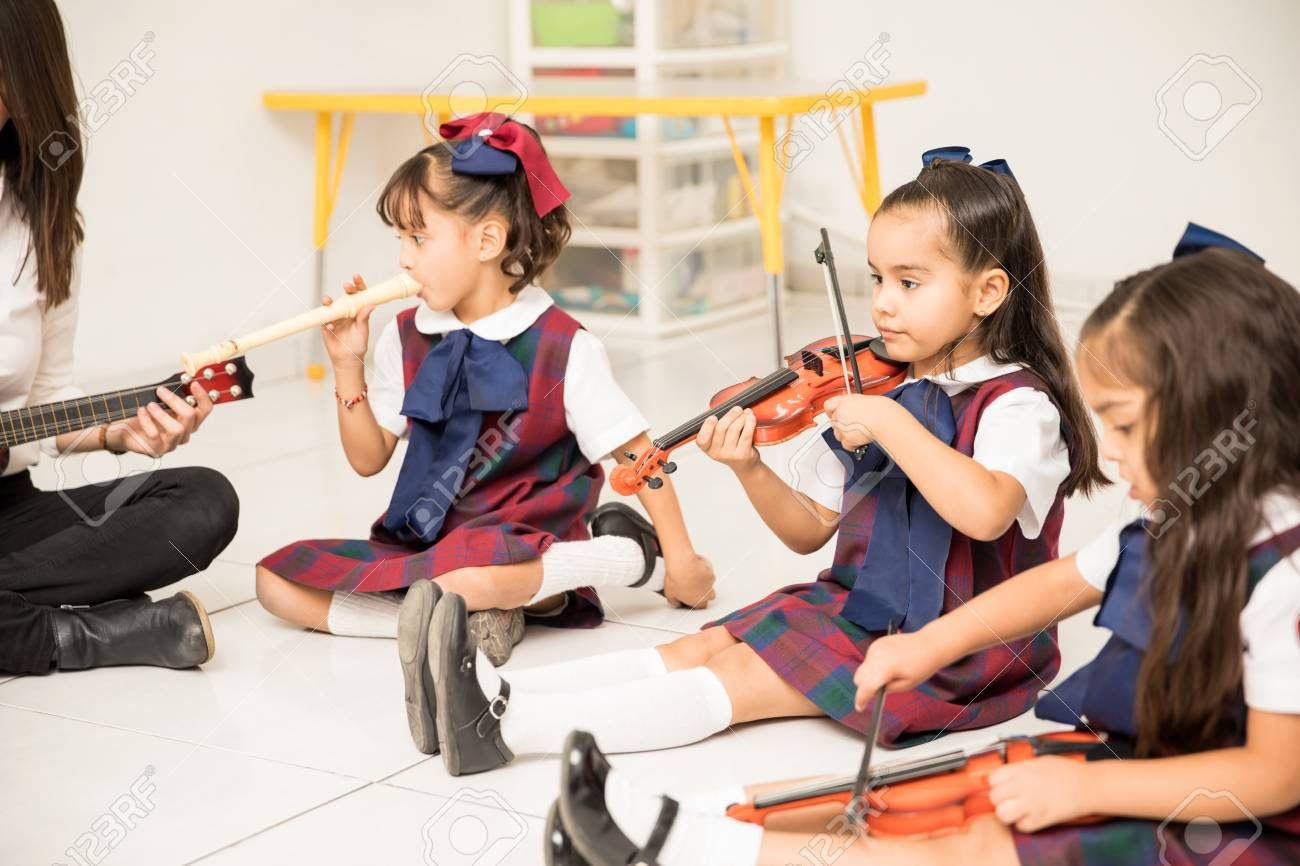 Pretty Latin girls in a preschool class learning some music with their teacher - 91940773