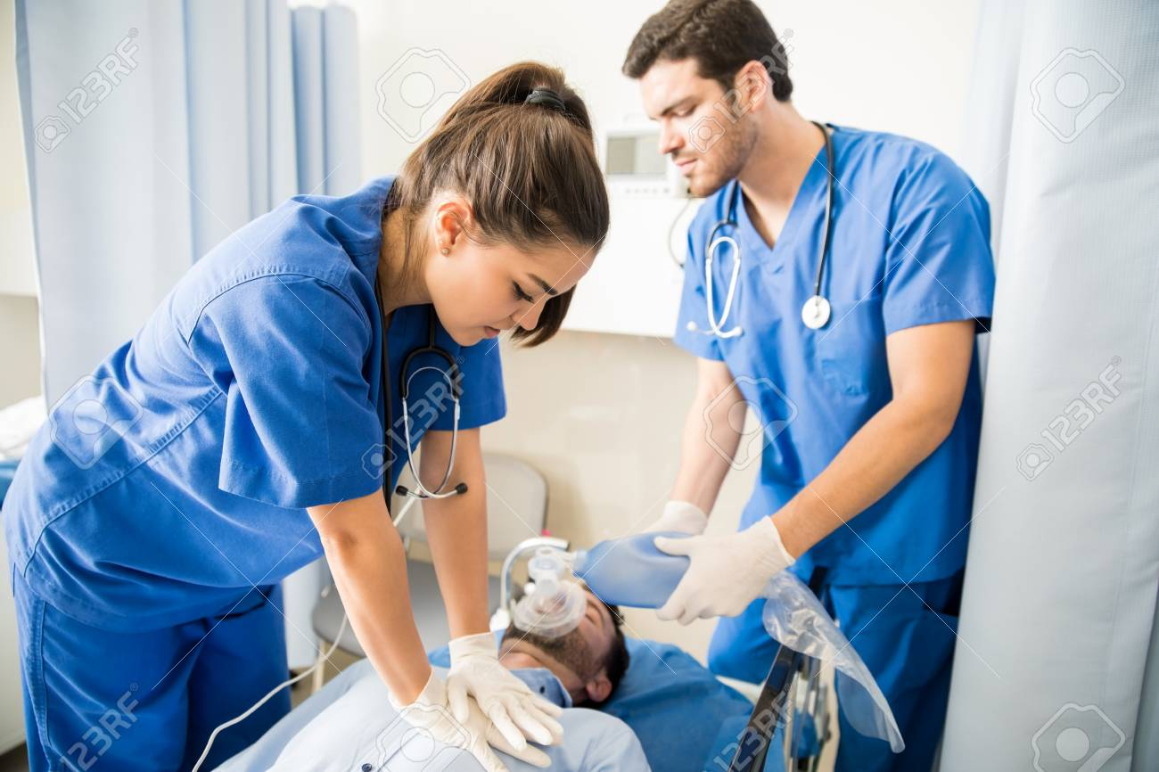 Two doctors giving CPR to a unconscious male patient lying on