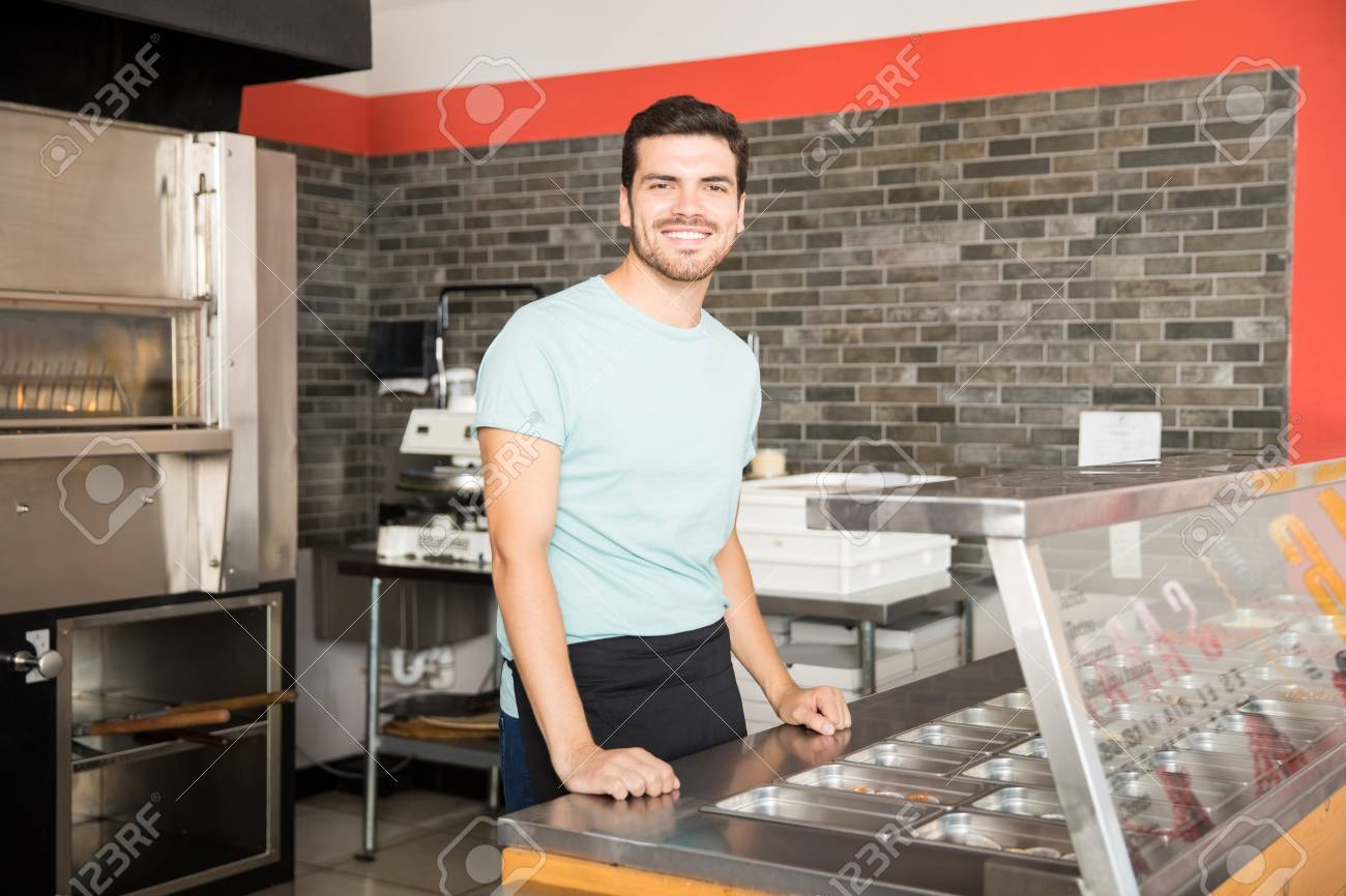 Young waiter in pizza shop standing behind counter smiling looking at camera - 104915401