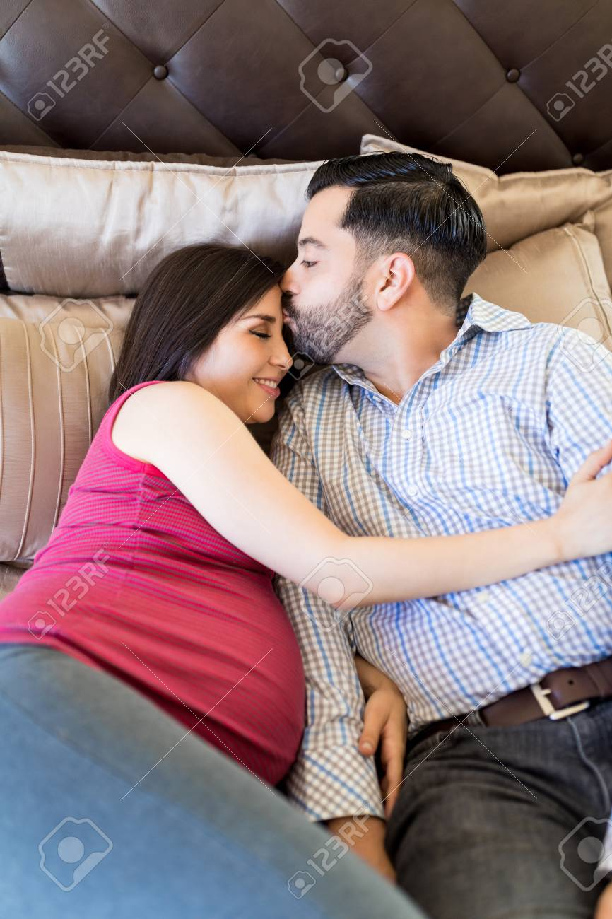 Hispanic Man Giving Good Night Kiss To Smiling Pregnant Woman