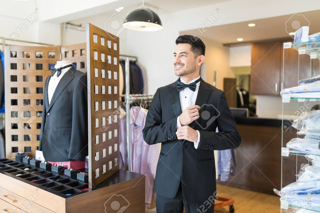Young customer getting ready for party in suit rental shop