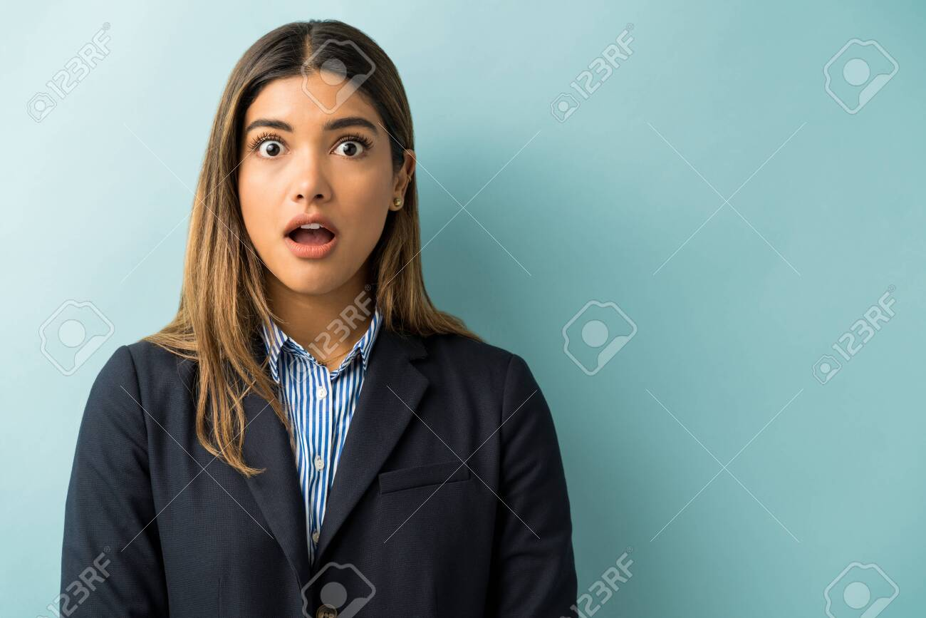 Beautiful Hispanic businesswoman standing with mouth open in shock at studio - 138553331