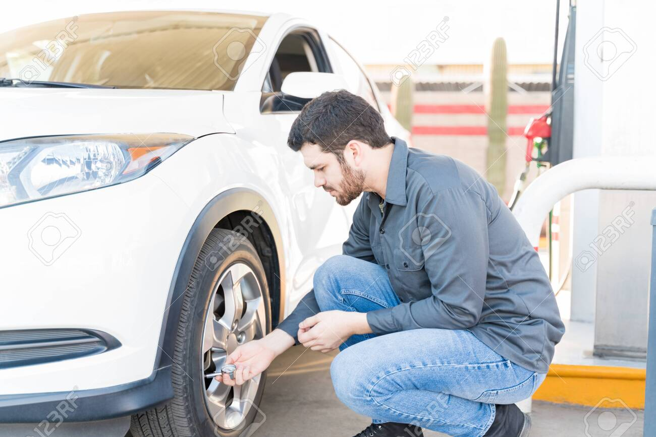 Side view of male gas station attendant checking air pressure of car tire - 139945652