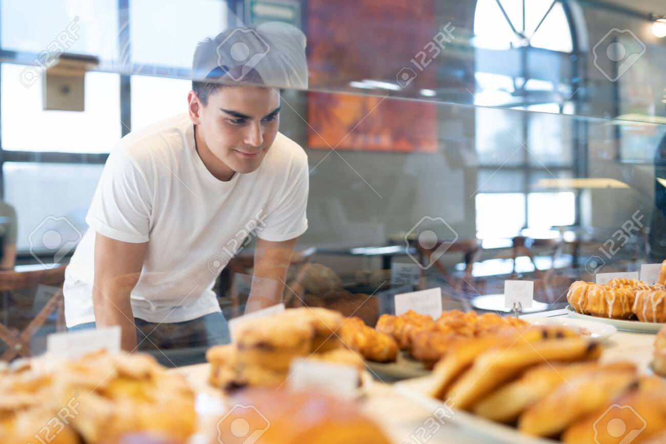 Attractive Hispanic man looking through a glass and choosing some bread and pastries in a bakery shop - 143744912