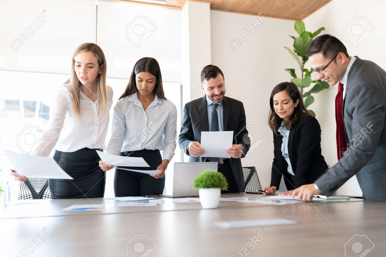 Group of male and female business associates with financial data reports during a meeting in office board room - 155328160