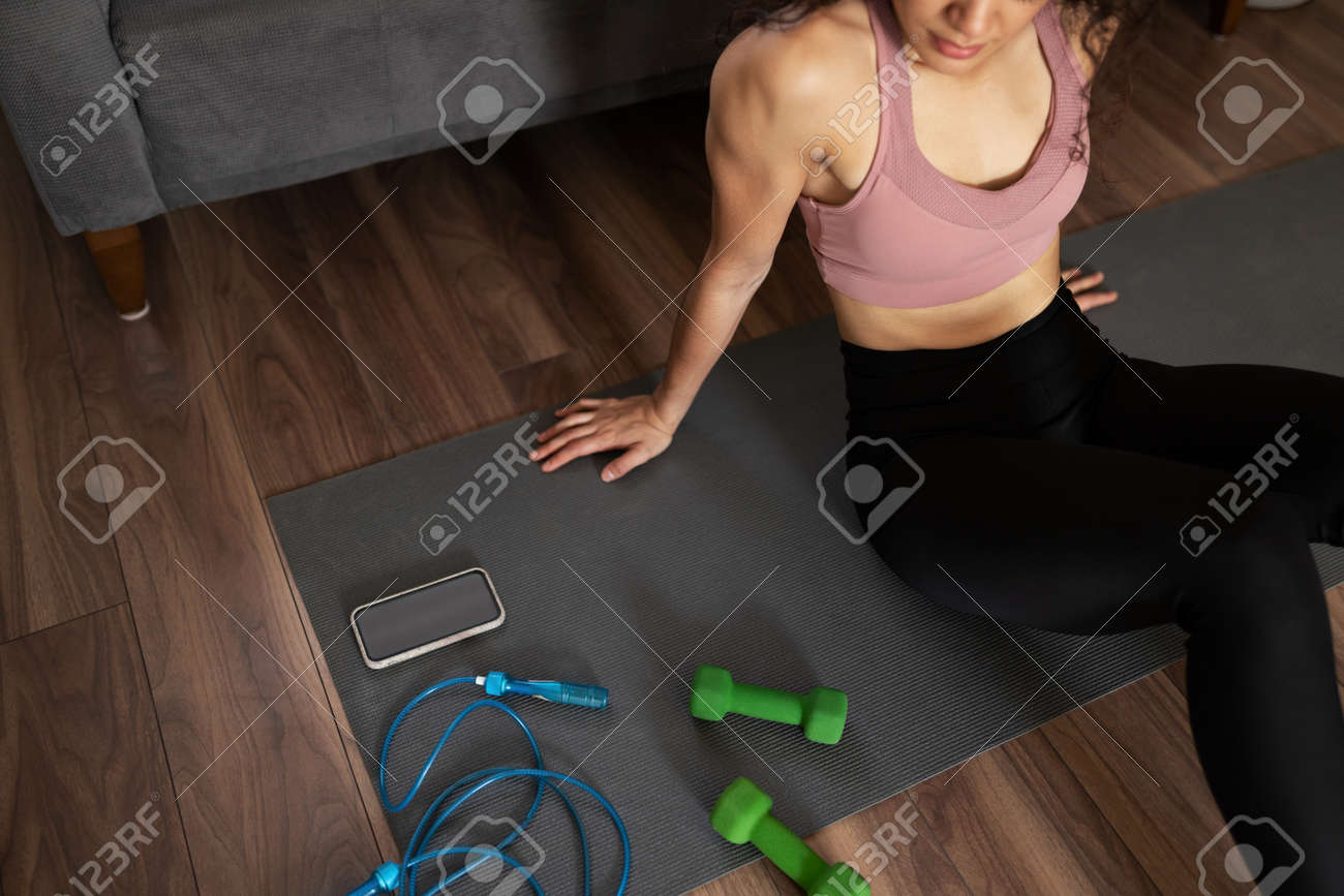 Strong woman in her 20s wearing activewear sitting in an exercise mat and preparing her home workout with dumbbells and a jump rope - 159706363