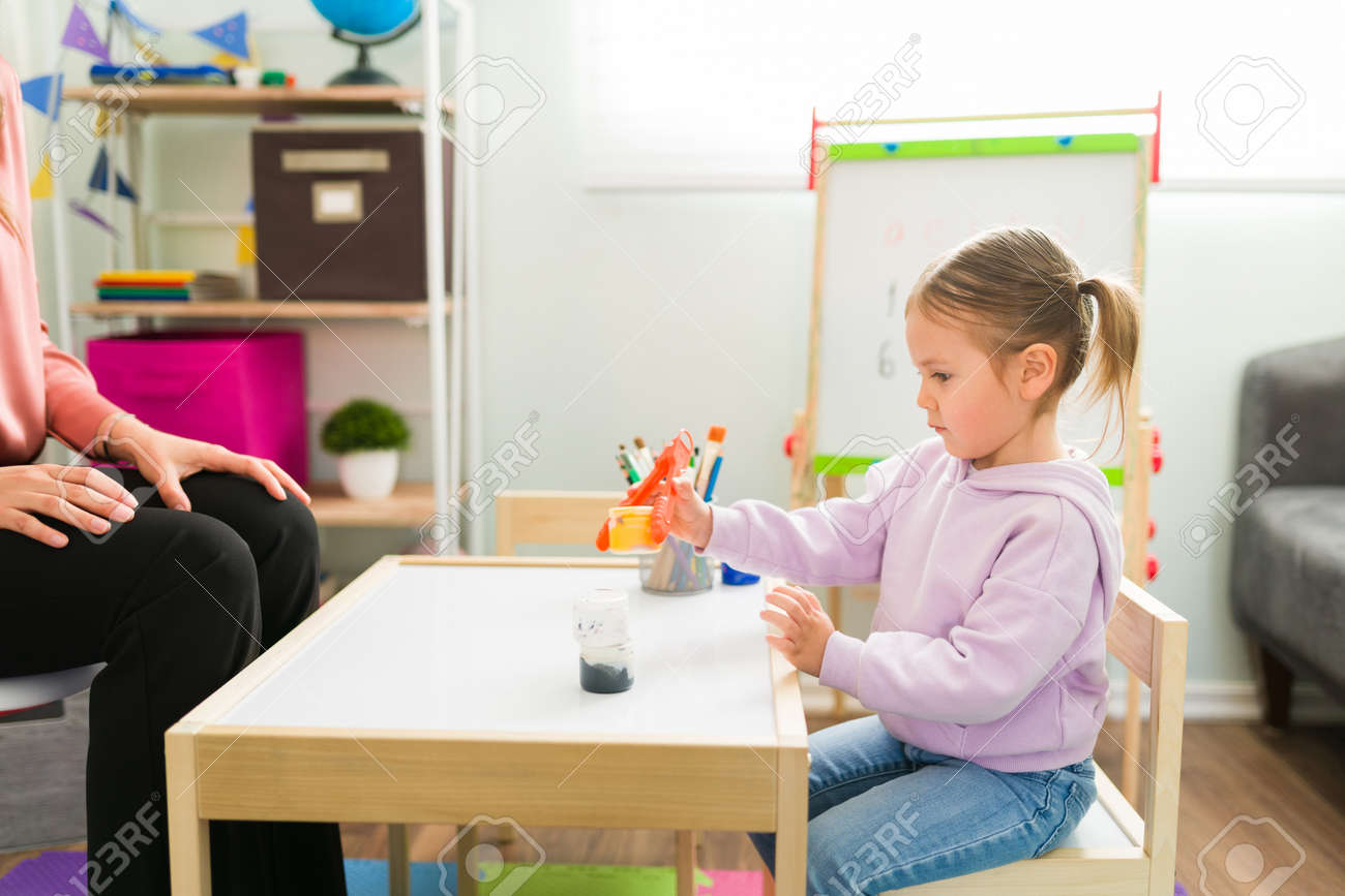 Beautiful girl holding a bottle with some tweezers during a day of homeschooling. Pretty girl learning and developing her fine motor skills - 164109296