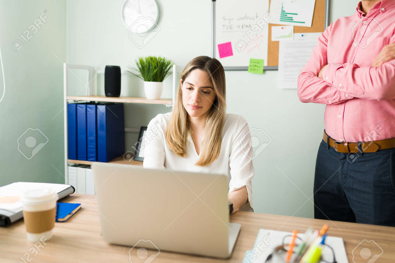 Upset male boss standing next to a female coworker and checking her work. Beautiful caucasian woman working and typing on a laptop at the office desk - 166342288