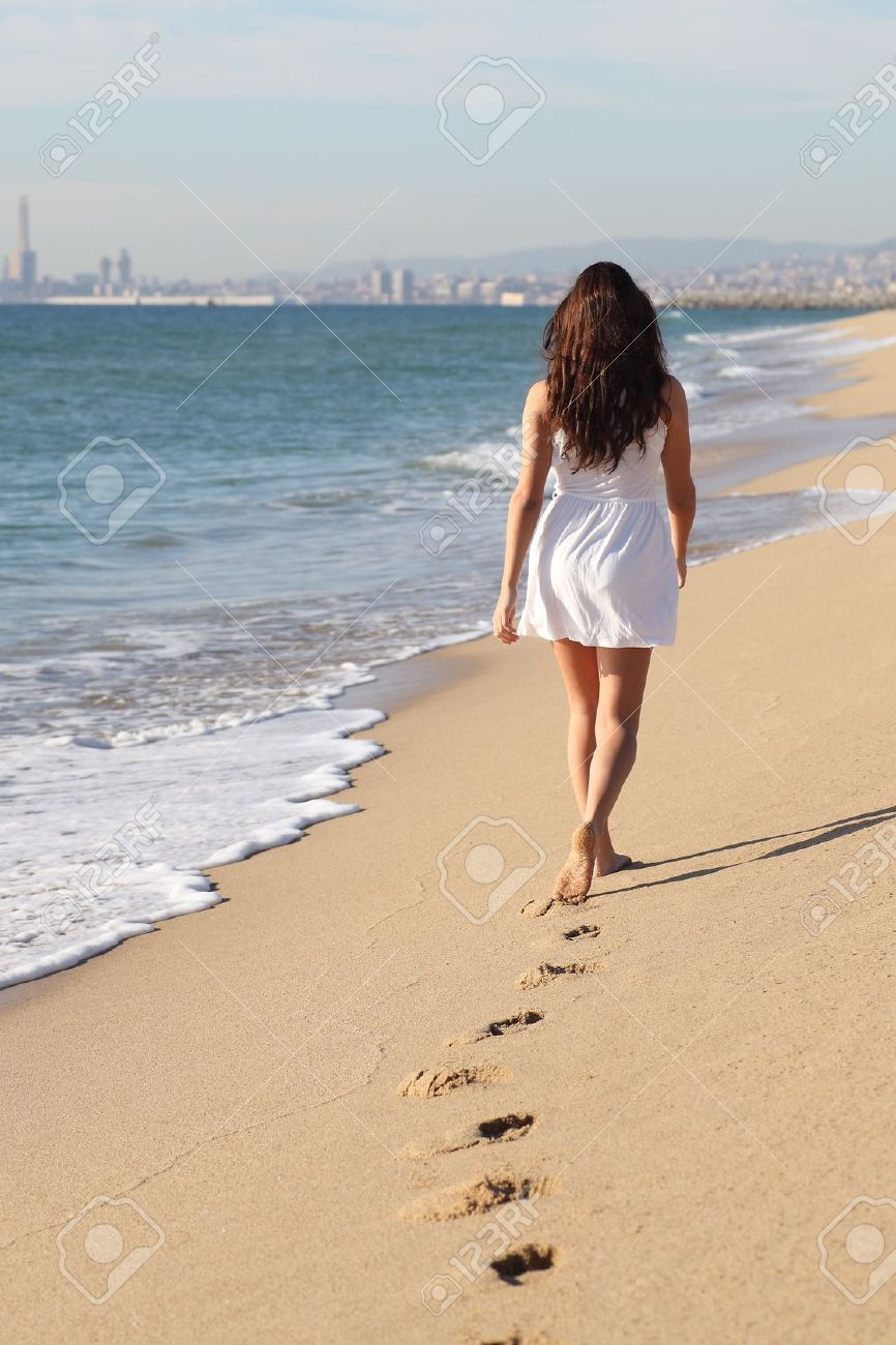 Woman walking on a beach royalty - Beautiful Woman Walking On The Beach With Her Footprints Back Stock Photo 17054698